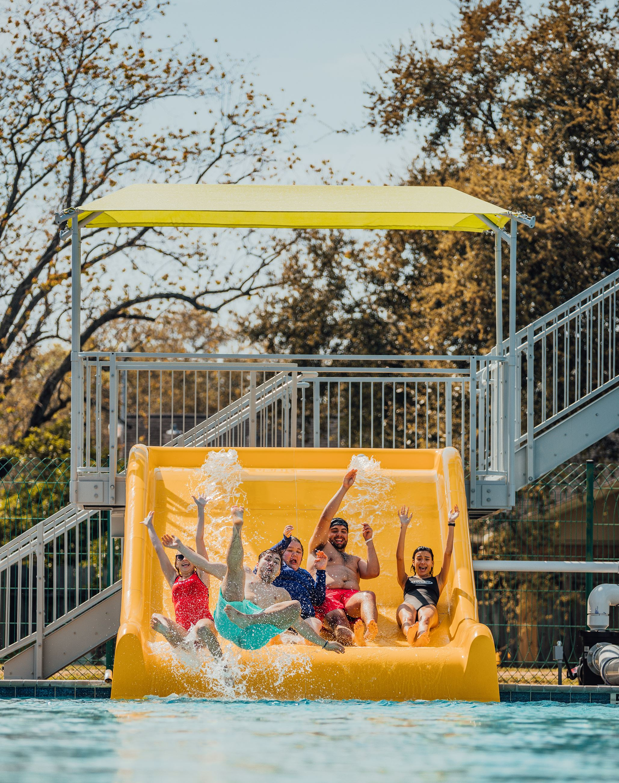 Five people sliding down giant slide into the pool
